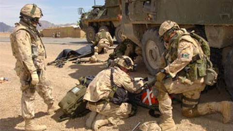 Canadian soldiers evacuate injured personnel after their armoured vehicle was struck by an oncoming vehicle outside of Kandahar City. The March 31, 2006, incident wounded two Canadian soldiers. (Robin Mugridge/Combat Camera/Canadian Forces)