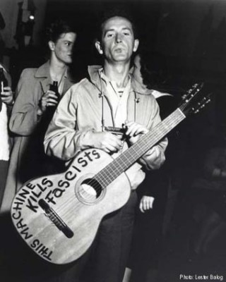 "Woody Guthrie with nylon string 00 circa 1941 with ""This Guitar Kills Fascists"""