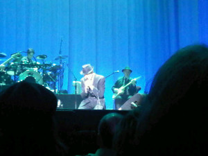 Leonard Cohen kneeling in performance, Halifax NS April 2013 (Blackberry photo)